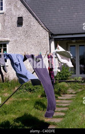 Washing line with clothes in cottage garden. This is the traditional way of drying clothes, bright sun and a good - Stock Photo