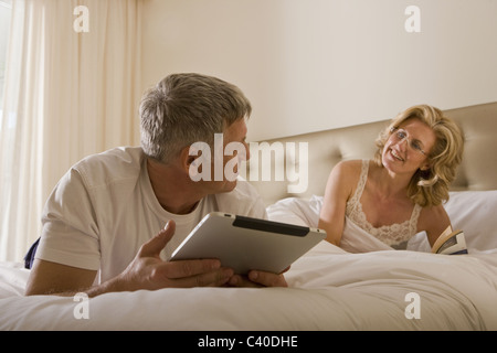 Man using tablet computer on bed - Stock Photo