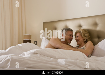 Mature couple embracing tenderly in bed - Stock Photo