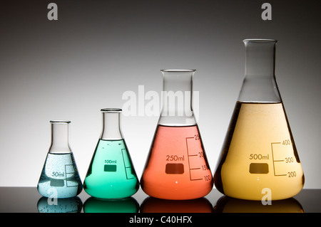 group of four flasks with colored liquid and a white background - Stock Photo