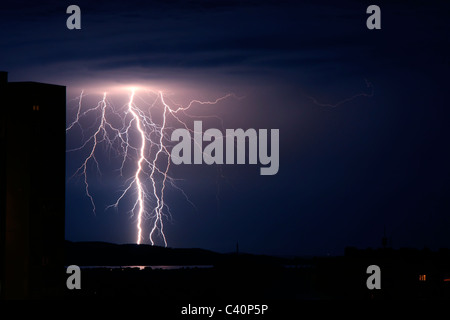 Lightning storm strikes over city and sea - Stock Photo