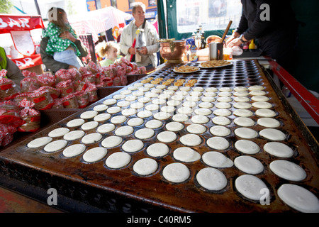 making dutch pancakes on a traditional hot plate on a market stall - Stock Photo