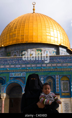 A veiled Arab woman holding her baby in front of the Dome of the Rock on the Temple Mount in Jerusalem. - Stock Photo