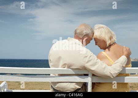 senior caucasian couple sitting on bench near the sea and hugging. Horizontal shape, rear view, copy space - Stock Photo