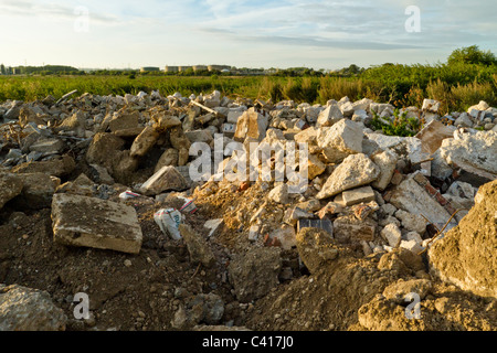 Fly tipping of construction waste. Illegally dumped rubble at the end of a countryside lane in Nottinghamshire, - Stock Photo