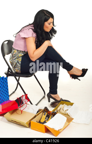 Woman sitting on chair in a shop place trying new shoes model - Stock Photo