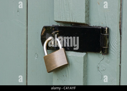 Old hasp and padlock, on an old shed door. - Stock Photo