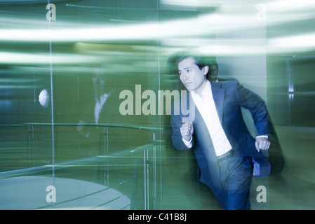 Businessman running in lobby - Stock Photo