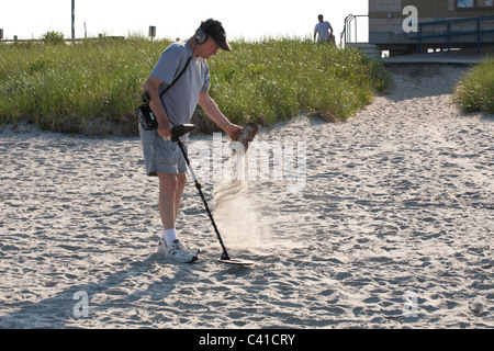 Searching the Sand. A man with a metal detector sifts through the sand at Long Beach Nahant just north of Boston. - Stock Photo