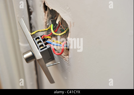 a faulty house light dimmer switch pulled away from wall showing electrical wires in parallel during DIY - Stock Photo