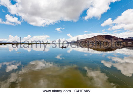 A small boat with reflections and clouds on Lake Titicaca, near Puno, Peru, South America. - Stock Photo