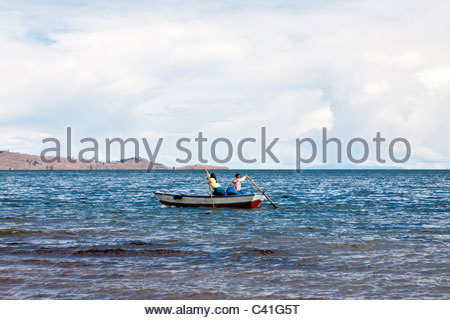 Two Aymara woman in a small boat on Lake Titicaca, near the community of LLachon on the Capachica Peninsula, near - Stock Photo