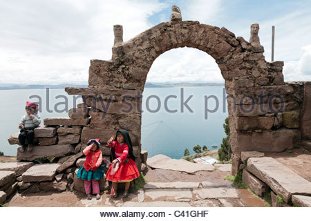 Three children sitting on the stone archway on the top of Taquile Island. Lake Titicaca, near Puno, Peru. - Stock Photo