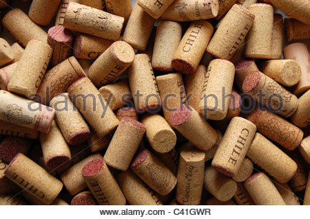 closeup overhead natural light studio shot pile of assorted red wine corks randomly placed many with Chile stamp - Stock Photo