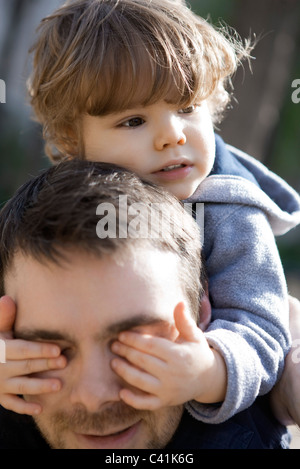 Toddler boy covering father's eyes with his hands, portrait - Stock Photo