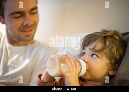 Toddler boy with father, drinking milk from baby bottle - Stock Photo