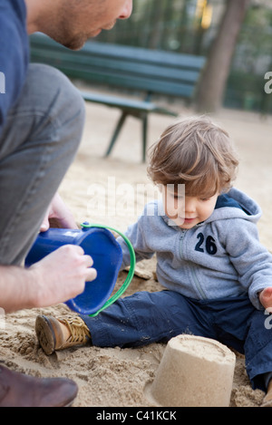 Toddler boy playing in sand with his father - Stock Photo