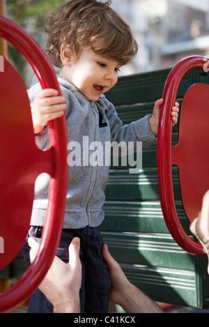 Toddler boy playing on playground - Stock Photo