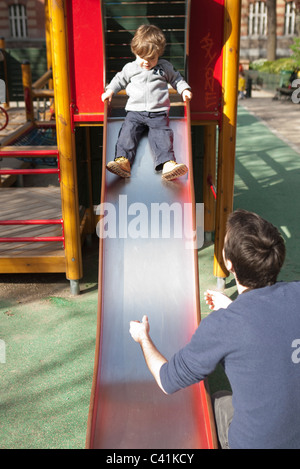Toddler boy preparing to go down playground slide, father waiting at the bottom - Stock Photo