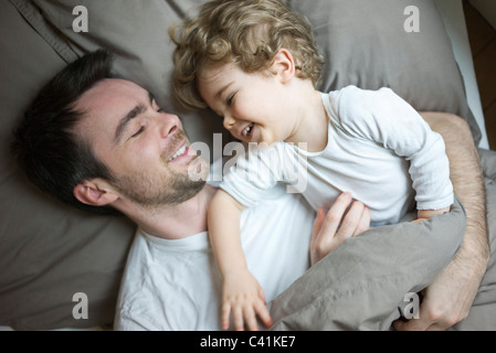 Father and young son relaxing together in bed, portrait - Stock Photo