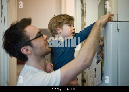 Toddler boy helping father using microwave - Stock Photo