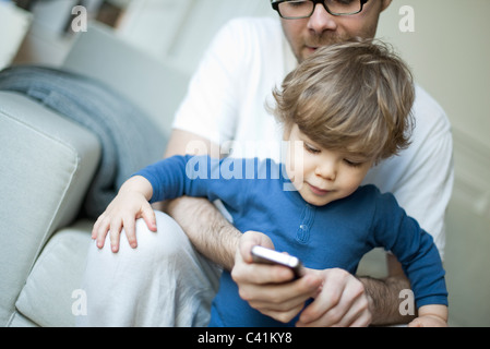 Toddler boy watching father using cell phone - Stock Photo