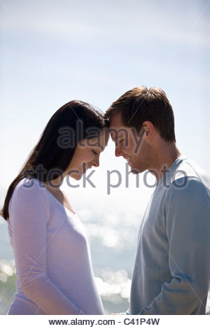 A pregnant woman and her partner on the beach, heads touching - Stock Photo