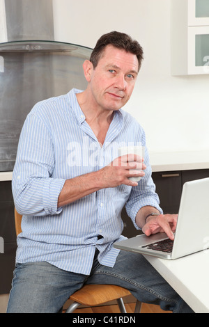 Man with tea or coffee in hand sitting at home in the kitchen using a laptop, looking at camera - Stock Photo