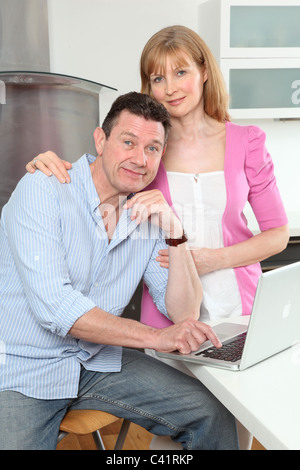Couple smiling looking to camera using a laptop in the kitchen - Stock Photo