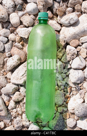 one,old,green,dumbed,plastic,bottle,on,a,pebble,rocky,beach,High angle view of an empty bottle on pebbles - Stock Photo