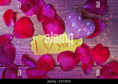 a heart of stone with petals of a rose and a love letter - Stock Photo