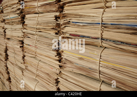 Close-up of piles of newspapers on an angle to be recycled - Stock Photo