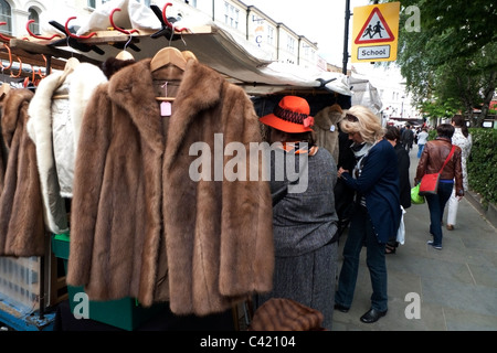 A woman shopping and market trader on a vintage fur coat jacket for sale on a Portobello Road  antique clothing - Stock Photo