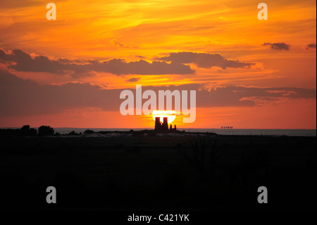 Sunset behind Reculver Towers and Shivering Sands Army Fort in Kent - Stock Photo