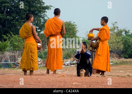 A group of Buddhist monks are standing on a dirt road while receiving rice from a woman in communist Laos. - Stock Photo