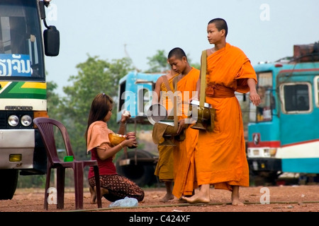 A group of Buddhist monks are walking on a dirt road while receiving rice from a woman in communist Laos. - Stock Photo