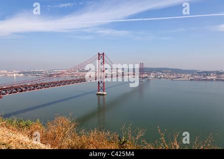 25 de Abril suspension bridge. Lisbon, Portugal. river red Lisboa landmark ponte painted Tagus rio tejo April 25th - Stock Photo