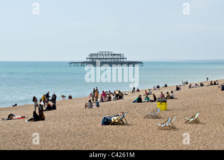 People relaxing on Brighton beach. - Stock Photo