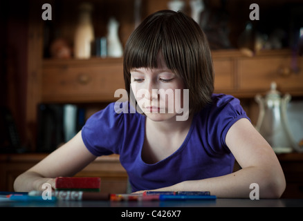 10 year old girl working on school home work - Stock Photo
