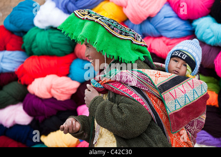 Peru, Huancarani, Woman and child in front of wool for sale on market. - Stock Photo