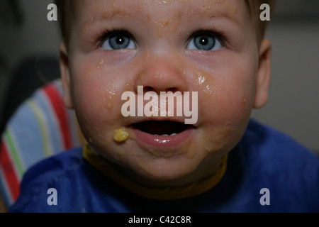 Close up of young child with food all over her face - Stock Photo