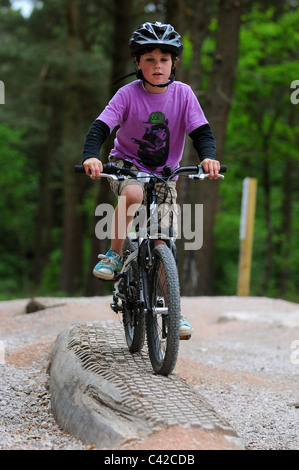 A young boy rides his mountain bike along a log at Haldon Forest Park in Devon. - Stock Photo