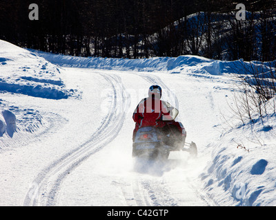 Driving snowmobile on forest road Finland - Stock Photo