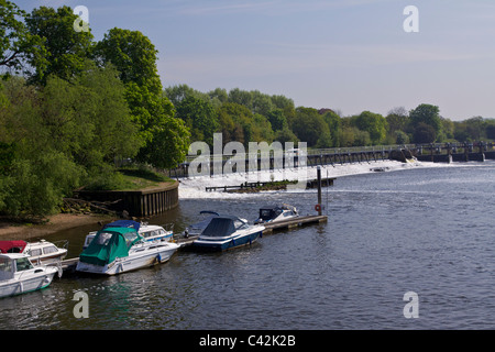 Teddington weir and the river Thames at high tide with boats moored by an eyot,  in the afternoon sun - Stock Photo
