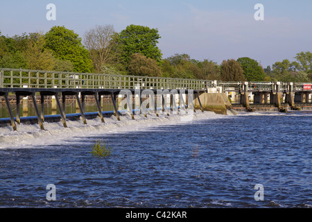 The weir at Teddington in the river Thames showing the tidal waters with trees in the background on a sunny afternoon - Stock Photo