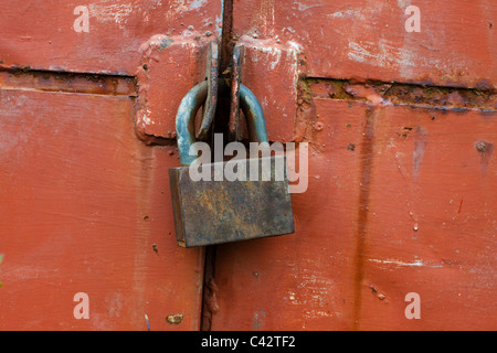 old rusty padlock on the red wall - Stock Photo