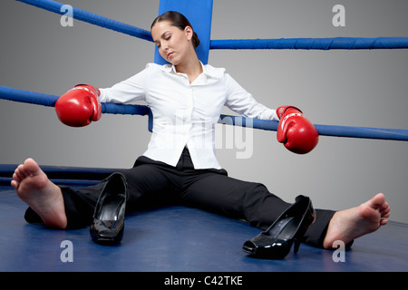 Portrait of tired businesswoman in boxing gloves sleeping on boxing ring - Stock Photo