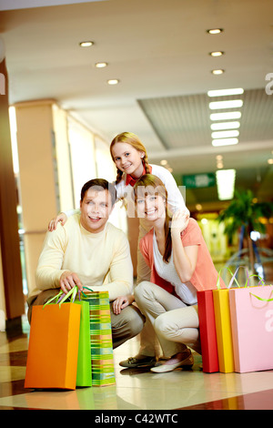Image of family with paperbags looking at camera in the mall - Stock Photo