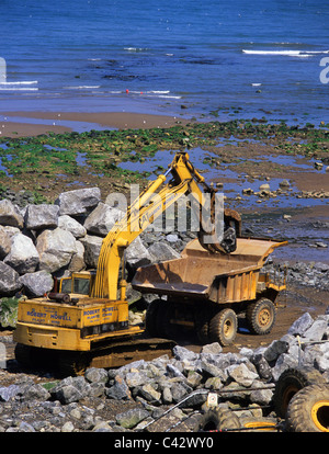 heavy machinery moving giant stone boulders building sea defences at North Bay Scarborough Yorkshire UK - Stock Photo