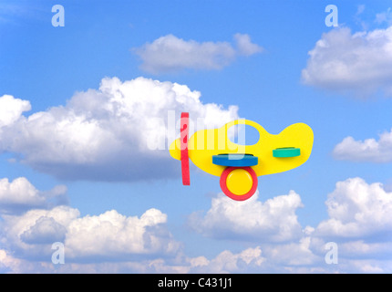 toy aeroplane cut-out against blue sky background with clouds - Stock Photo